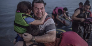 A Syrian refugee from Deir Ezzor, holding his son and daughter, breaks out in tears of joy after arriving via a flimsy inflatable boat crammed with about 15 men, women and children on the shore of the island of Kos in Greece, Aug. 15, 2015. *ON EMBARGO UNTIL AUGUST 27, 2015.* *** Local Caption *** 14706734